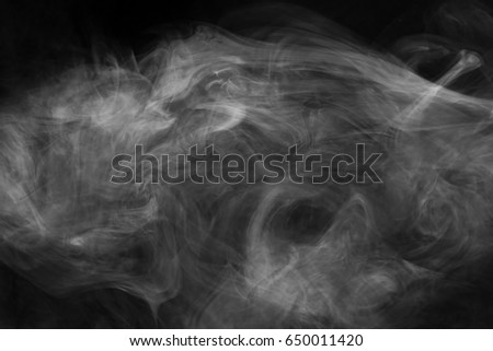 Smoke diffusing in ray of sunlight.