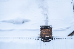 Smoke flies from the chimney in the winter during the day. Roof covered with snow in Lviv.