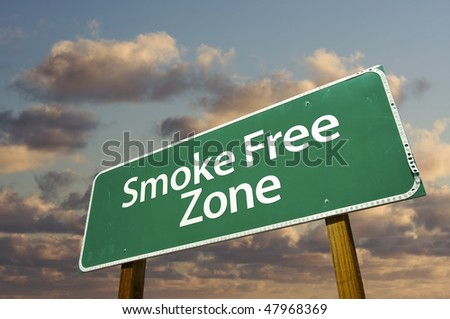Smoke Free Zone Green Road Sign In Front of Dramatic Clouds and Sky.