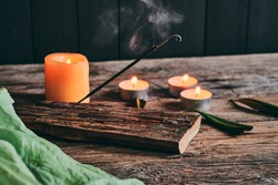 Smoke from incense stick and relaxing candles on rustic wood