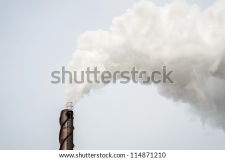 Smoke from metal chimney drifting in the wind