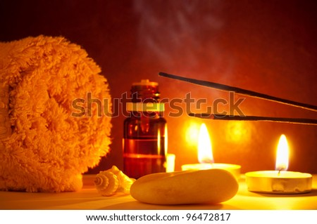 Smoke from scented sticks, towel, candles and essential oil bottle