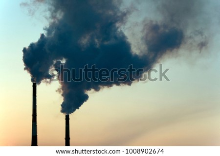 Smoke from two industrial chimneys (pipes) against the orange - blue sky. Global warming. Air polution.