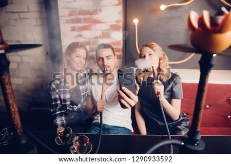 Smoke hookah shisha in bar and nightclub, team of friends take selfie photos on phone.