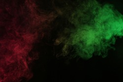 Smoke in red-green light on black background in darkness