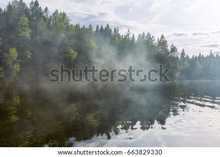 Smoke on the lake, summer in Finland #663829330