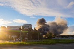 Smoke over enterprise. Smoke over industrial building. Smoke from fire against sky. Industrial factory on fire. Fume clubs in distance. Burning building on summer day. Fume over factory building