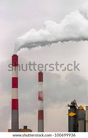 Smoke rising from power plant against sky