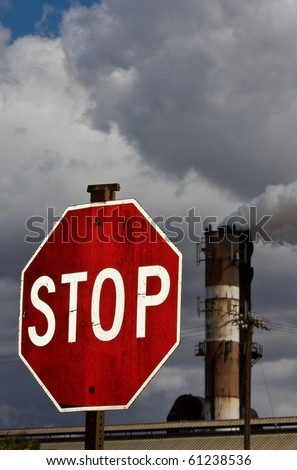 Smoke stack with STOP sign in foreground - environmental concept