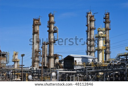 Smoke stacks at oil refinery against blue sky. - stock photo