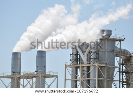 Smoke stacks billowing out steam and vapor from a manufacturing facility