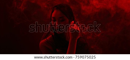Stock Photo Smoke Tan Skin Asian Woman black hair dark lip with Dense Fluffy Puffs of White Smoke and Fog on dark Background, Abstract Smoke girl mysterious Clouds, and under low exposure contrast, copy space