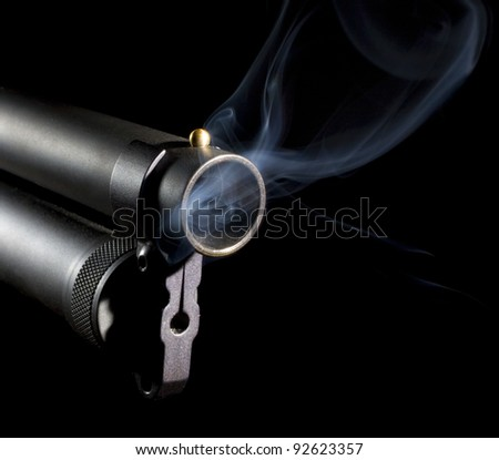 smoke that is coming from a 12 gauge shotgun barrel that is rising