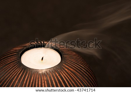 Smoke trails from a candle as its flame is extinguished. On a dark background, with short depth of field.