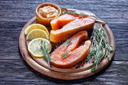 Smoked arctic char steaks on a round cutting board  on a dark wooden background with cod roe, lemon, fresh rosemary, peppercorn, top view, close-up