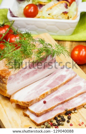 Smoked bacon. Arrangement with meat smoked bacon, tomatoes and  spices on cutting board