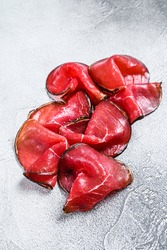 Smoked bresaola beef cut pieces, Italian Antipasti. White background. Top view