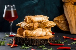Smoked cheese pigtail on сross section of tree trunk on black table background with beer glass and chili pepper.