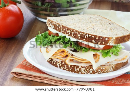 Smoked chicken or turkey sandwich with lettuce, tomato and swiss cheese and whole grain bread.