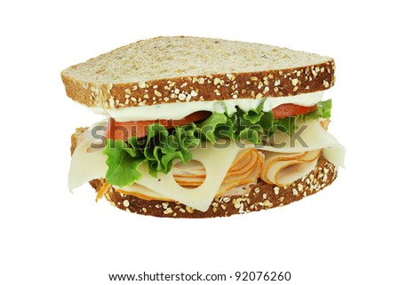 Smoked chicken sandwich with lettuce, tomato and swiss cheese on whole grain bread isolated on a white background. Clipping path included.