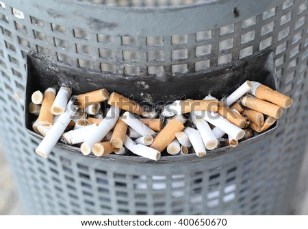 Smoked Cigarettes Butts in a Dirty Ashtray Big Bin Stock fotó ©
