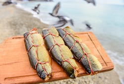 Smoked fish on a wooden board against the background of the sea and a flock of flying birds