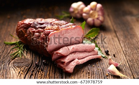 Smoked ham on a wooden rustic table with addition of fresh aromatic herbs and spices, natural product from organic farm, produced by traditional methods,