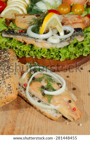Smoked mackerel fillet, garnished with onion rings, in whole wheat bread, with lettuce on a wooden chopping board
