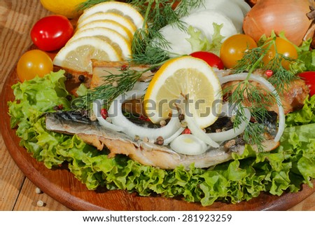 Smoked mackerel fillet with salad, lemon, onions, tomato, garnished with dill on a wooden kitchen board