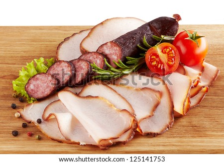 smoked meat and sausages on wooden cutting board