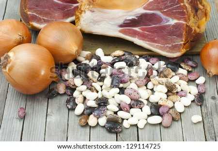 smoked pork ham, beans and onions, bean soup ingredients on rustic wooden