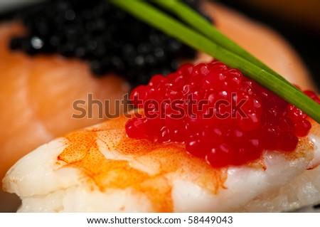 Smoked salmon and prawn nigiri and norimaki sushi garnished with red and black fish eggs and chives.