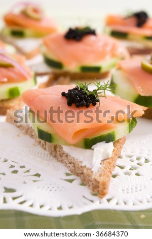 Smoked salmon canapes on rye bread with cream cheese, cucumber, black caviar, and fresh dill.
