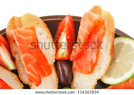 smoked salmon on baguette with olives and pepper