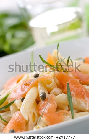 Smoked Salmon Penne (tube-shaped pasta) with capers, tarragon and cheese creamy sauce. Caesar salad and glass of white wine out of focus. Shallow DOF