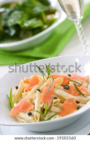 Smoked Salmon Penne (tube-shaped pasta) with cappers, tarragon and cheese creamy sauce. Caesar salad and glass of white wine out of focus. Shallow DOF - stock photo