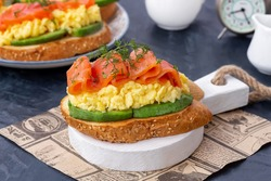 Smoked salmon, scrambled eggs and avocado toasts. Healthy breakfast concept. Dark background, close-up, selective focus.