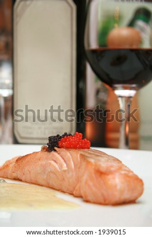 Smoked salmon slice with black and red caviar accompanied by a light butter and pepper sauce