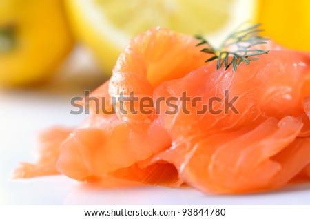 Smoked salmon with dill, lemons in the background - stock photo