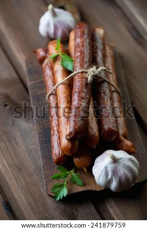 Smoked sausages with fresh parsley and garlic, studio shot