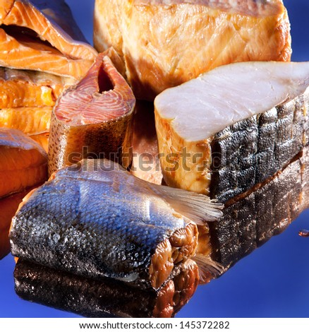 Smoked sliced salt different fish on blue mirror background
