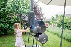 Smoker grill in home backyard, container with coal, smoke coming out of a smokestack, barbecue on green background, family patio, outdoor bbq party on open air