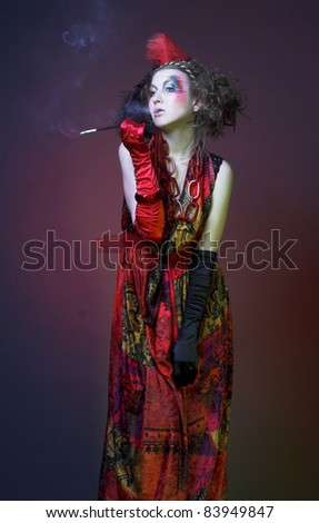 Smoker. Young woman in creative vintage image in velvet dress and gloves.