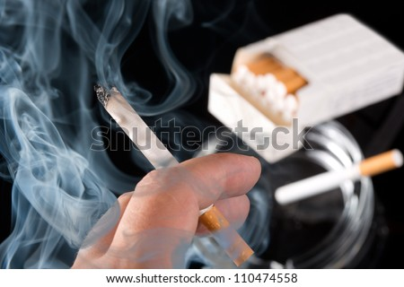 Smokers hand with ashtray and cigarettes pack on background
