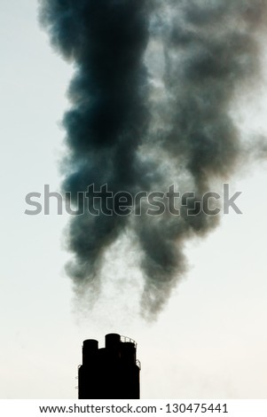 Smokestack chimneys belching black smoke  pollutants and greenhouse gas into the atmosphere polluting and contributing to global warming