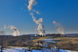 Smokestack emissions from coal-fired powerplants photographed against a rural West Virginia backdrop under a clear blue sky