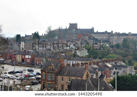 Smokey rooftop view of old row homes in ancient Armagh city, Northern Ireland, UK. Deep, rich colors set against grey winter sky.  #1443205490
