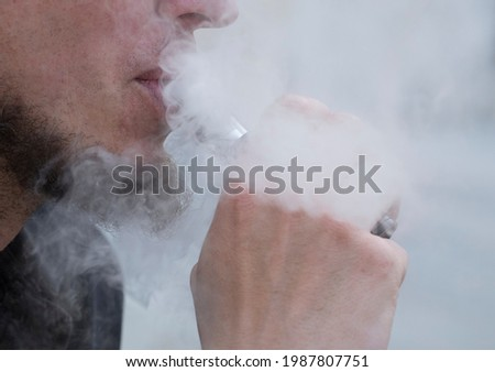 smoking an e-cigarette or electronic cigarette, nicotine consumption and vaping Сток-фото ©