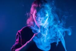 Smoking an electronic cigarette. The girl's face is covered with smoke from vape. Portrait of a female smoker in a cloud of smoke. A woman smokes a VAPE on a dark background.