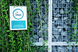 Smoking area sign board hang on plant wall and rock fence in park, faded sign at outdoor zone for smoke.